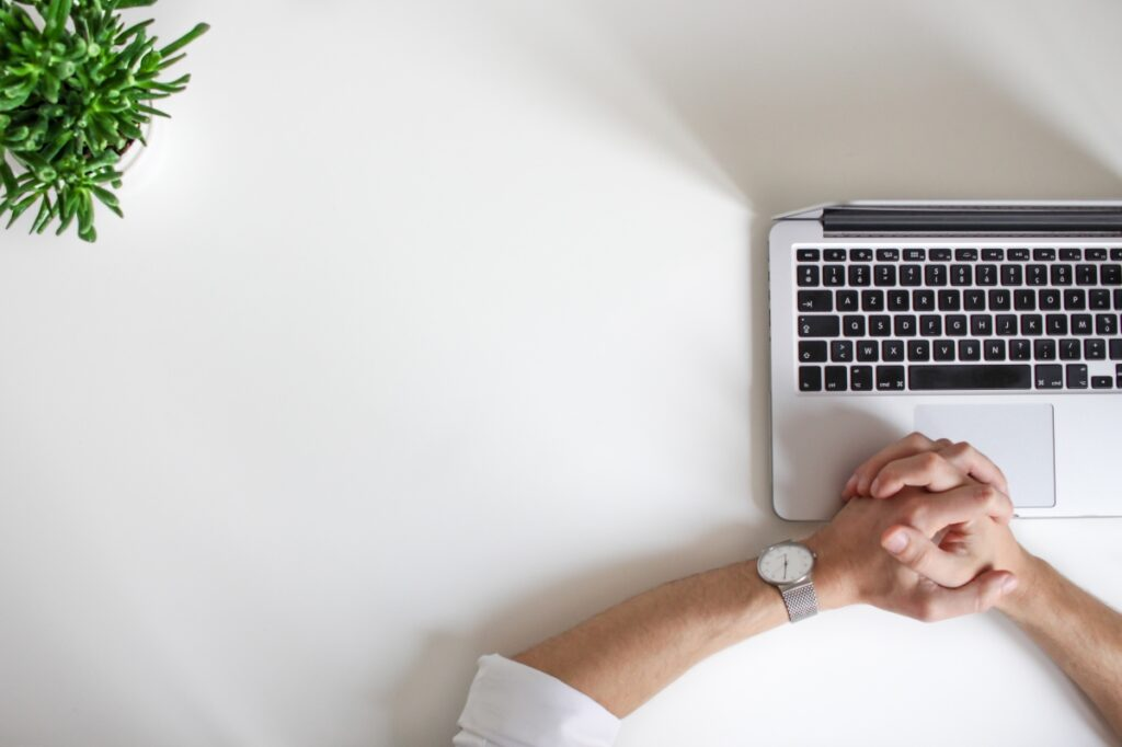 A Man Holding His Hands Waiting At His Laptop
